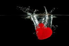 Rotes Herz, das auf das Wasserspritzen fällt Stockfotografie