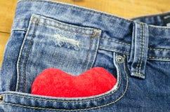 Rotes Herz, das aus einer vorderen Tasche der Jeans heraus haftet Stockfotografie