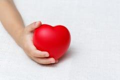 Rotes Herz in den Babypalmenhänden Lizenzfreies Stockbild