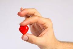 Rotes Herz in den Fingern des Mannes Lizenzfreie Stockbilder