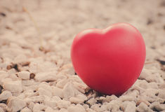 Rotes Herz in der Liebe des Valentinstags mit weißem Steinhintergrund Lizenzfreie Stockfotos