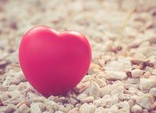 Rotes Herz in der Liebe des Valentinstags mit weißem Steinhintergrund Stockbild