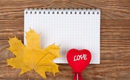 Rotes Herz des gelben Blattes auf einem hölzernen Hintergrund Stockfoto