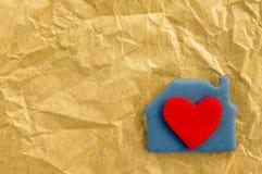 Rotes Herz in einem blauen Häuschen vom Plasticine auf dem zerknitterten gemachten alten Papier Lizenzfreies Stockbild