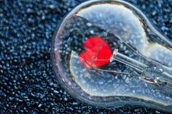 Rotes Herz einer elektrischen Birne Stockbild