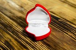 Rotes Herz-förmiges Schmuckkästchen auf einem Holztisch Lizenzfreie Stockfotos