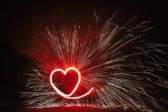 Rotes Herz formte Feuerwerk mit Scheinen auf schwarzem Hintergrund in n lizenzfreie stockfotos