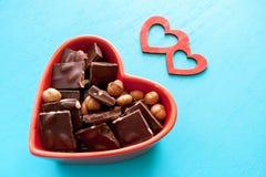 Rotes Herz formte Schüssel mit Schokolade und zwei Herzen auf Türkis stockfoto