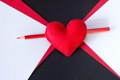Rotes Herz gemacht vom Filz auf einem schwarzen Hintergrund Lizenzfreie Stockfotografie