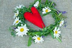 rotes Herz gemacht vom Filzgewebe und ein Kranz von Feldblumen Lizenzfreies Stockbild