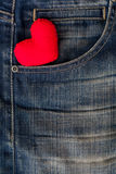 Rotes Herz gesetzt auf alte Blue Jeans Durchschnittliebe für Denim Stockbild