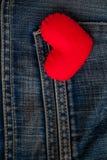 Rotes Herz gesetzt auf alte Blue Jeans Durchschnittliebe für Denim Stockbilder