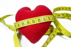 Rotes Herz mit dem Maß-Band, das sich herum kräuselt Lizenzfreies Stockfoto
