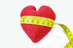 Rotes Herz mit dem Maß-Band, das sich herum kräuselt Lizenzfreie Stockfotografie