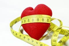 Rotes Herz mit dem Maß-Band, das sich herum kräuselt Stockbild