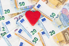Rotes Herz mit Euro Euroanmerkungen mit Reflexion Liebe und Geld Lizenzfreie Stockbilder