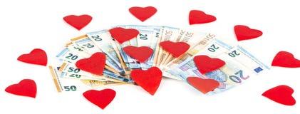 Rotes Herz mit Euro Euroanmerkungen mit Reflexion Liebe und Geld Stockbilder