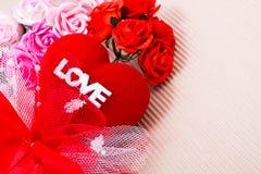 Rotes Herz mit Liebeswort und -rosen Stockfotografie