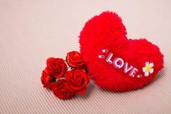 Rotes Herz mit Liebeswort und -rosen Lizenzfreie Stockfotos