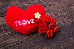 Rotes Herz mit Liebeswort und -rosen Stockbild