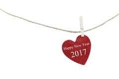 Rotes Herz mit Text des guten Rutsch ins Neue Jahr 2017, das am Hanfseil hängt Lizenzfreie Stockfotos