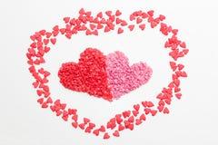 Rotes Herz nahe bei dem rosa Herzen gemacht von den kleinen dekorativen Herzen auf weißem Hintergrund Lizenzfreies Stockfoto