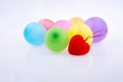 Rotes Herz und bunte kleine Ballone Stockfotos