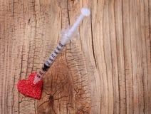 Rotes Herz und Spritze des Funkelns mit Droge über hölzernem Hintergrund. Lizenzfreies Stockfoto