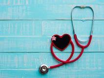 Rotes Herz und Stethoskop auf blauem hellem hölzernem Hintergrund heal stockbilder
