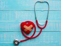 Rotes Herz und Stethoskop auf blauem hellem hölzernem Hintergrund heal stockfoto