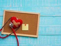 Rotes Herz und Stethoskop auf blauem hellem hölzernem Hintergrund heal stockfotografie
