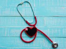 Rotes Herz und Stethoskop auf blauem hellem hölzernem Hintergrund heal stockfotos