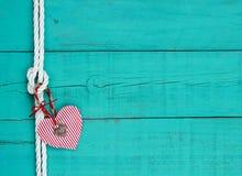 Rotes Herz und Verschluss, die am Seilknoten gegen blauen hölzernen Hintergrund der antiken Knickente hängt Lizenzfreie Stockfotos