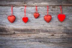 Rotes Herz verziertes Hängen am hölzernen Hintergrund Konzept Valent Stockfotos