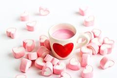 Rotes Herzsymbol auf Erdbeermilchschale und rosa Süßigkeitsherzen an Stockbilder