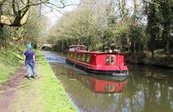 Rotes Kanalboot und -wanderer auf Leinpfad Lancaster-Kanal Stockbilder