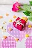 Rotes Kastengeschenk surronded durch Herzen und Blumen Stockfotos