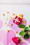 Rotes Kastengeschenk surronded durch Herzen und Blumen Stockbild