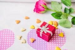 Rotes Kastengeschenk surronded durch Herzen und Blumen Stockfoto