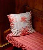 Rotes Kissen hielt auf einer hölzernen Bank Stockbilder