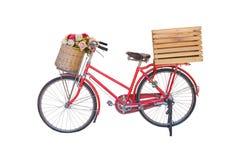 Rotes klassisches Fahrrad mit Blume im Korb und in der Kiste Lizenzfreies Stockbild