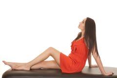 Rotes Kleid der Frau sitzen schauen zurück oben lizenzfreie stockfotografie