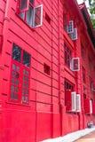 Rotes Kolonialgebäude mit roter Tür und roten Fenstern Lizenzfreie Stockbilder