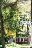 Rotes Kolonialhaus in der bewaldeten Einstellung Stockfoto