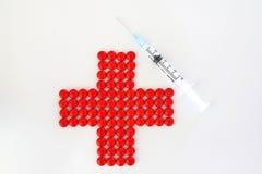 Rotes Kreuz gebildet mit roten Pillen und Spritze lizenzfreie stockbilder