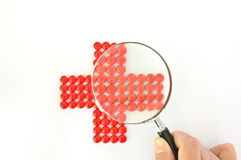 Rotes Kreuz gebildet mit roten Pillen und Vergrößerungsglas stockfotografie