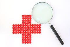 Rotes Kreuz gebildet mit roten Pillen und Vergrößerungsglas stockbild