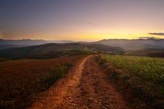 Rotes Land und Dorf im Sonnenuntergang Stockfotos