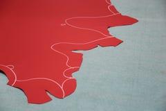 Rotes Leder mit Kreidemarkierungen auf grauer Oberfläche Lizenzfreies Stockbild