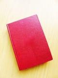 Rotes ledernes gebundenes Buch auf braune Tischplatte Lizenzfreie Stockfotografie